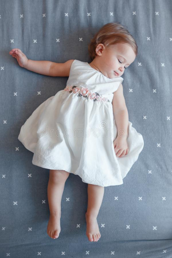 Free Caucasian Blonde Baby Girl One Year Old In White Dress Lying On Grey Bed Sheet In Bedroom, View From Top Royalty Free Stock Images - 109435119