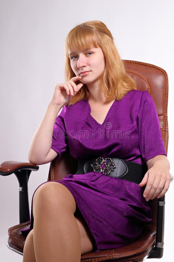Caucasian blonde girl sitting in an office chair stock images