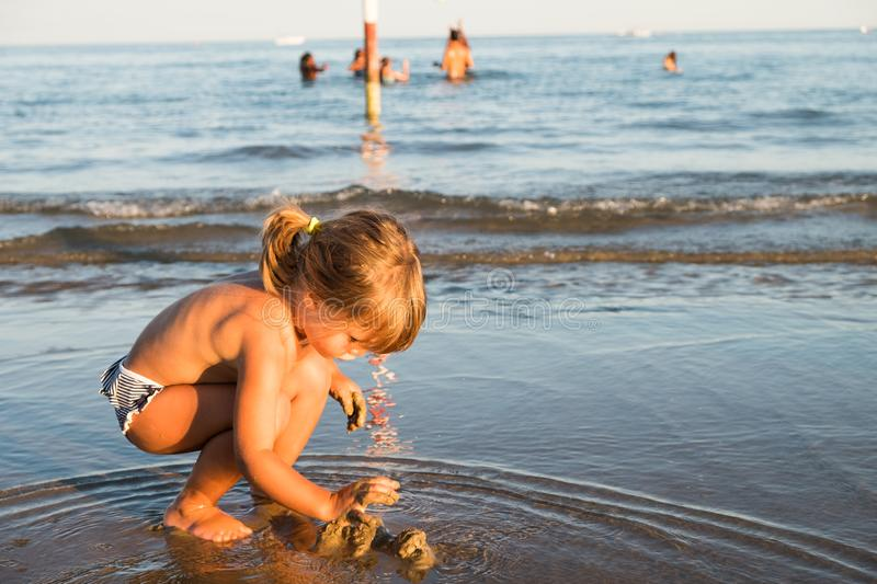Caucasian blonde little girl playing with sand stock photos