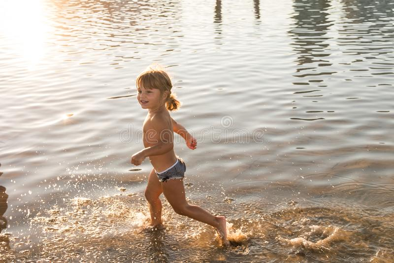 Caucasian blonde little girl running on the beach sand at sunset royalty free stock images