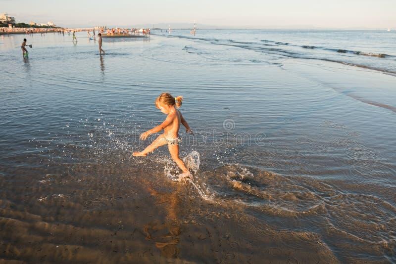 Caucasian blonde little girl running on the beach sand at sunset stock photography