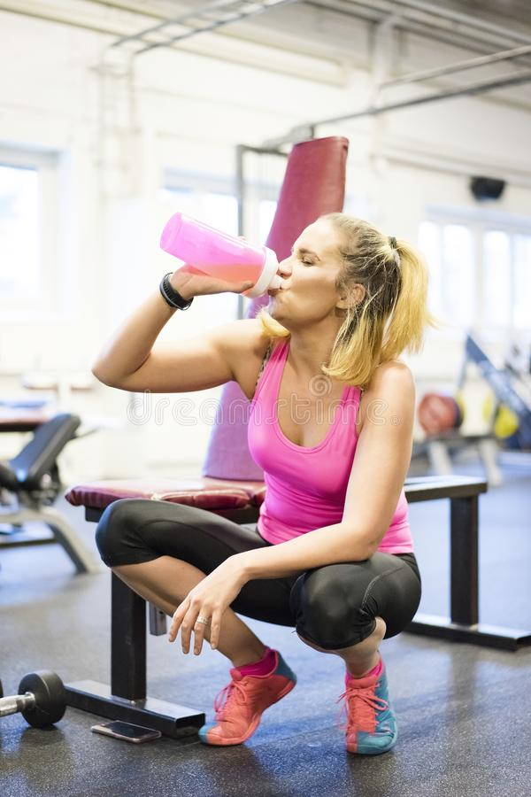 Caucasian blonde Scandinavian fitness girl training at gym drinking water stock photography