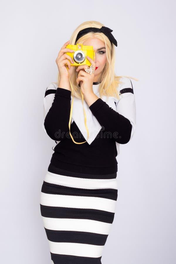 Caucasian blonde woman making shoot with yellow camera royalty free stock photo