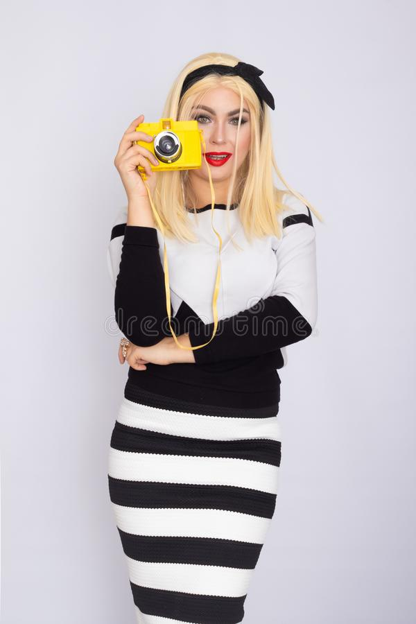 Caucasian blonde woman making shoot with yellow camera royalty free stock photography