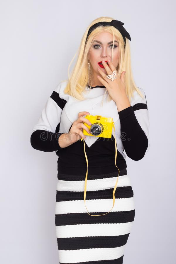 Caucasian blonde woman making shoot with yellow camera stock photography