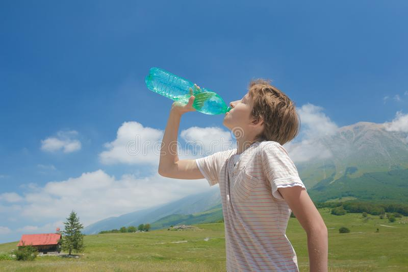 Caucasian boy drinking clear water from battle in his hands high in Alps royalty free stock images