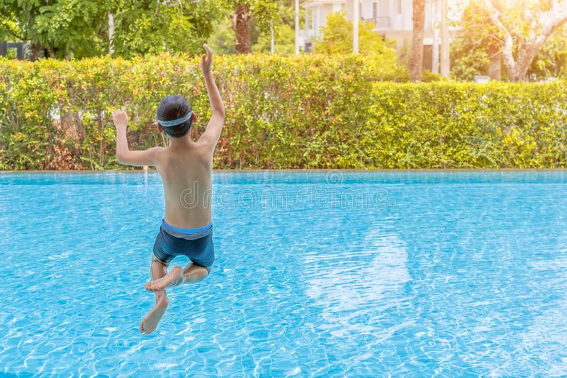 Caucasian boy having fun jumping into the pool. Happy boy kid jumping in the pool stock photo