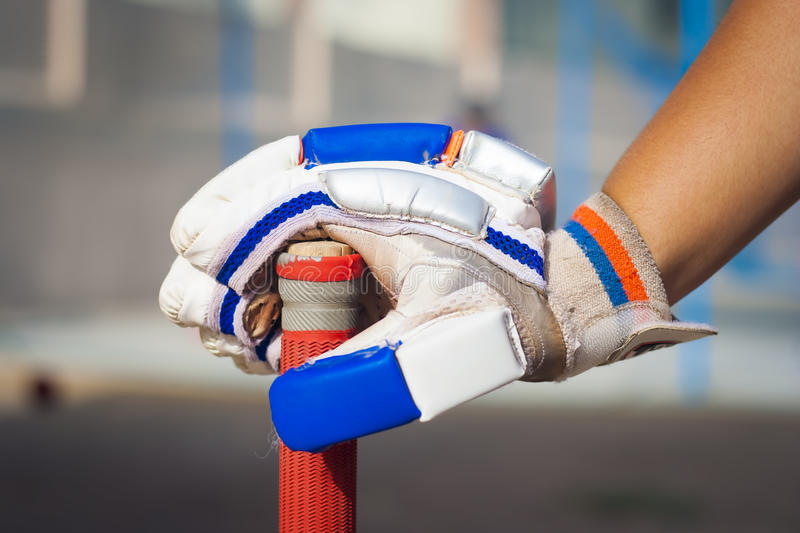 Caucasian boy holding cricket bat. & wearing red and white & blue color glove.isolated, selective focus, shallow depth of field, concept of sports & spirit stock image