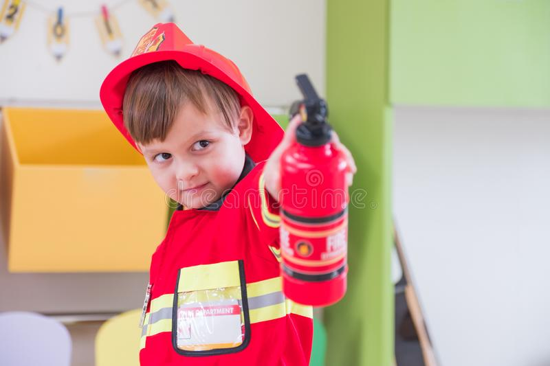 Caucasian boy kid dress up to fireman and use speaker at roll pl stock photos
