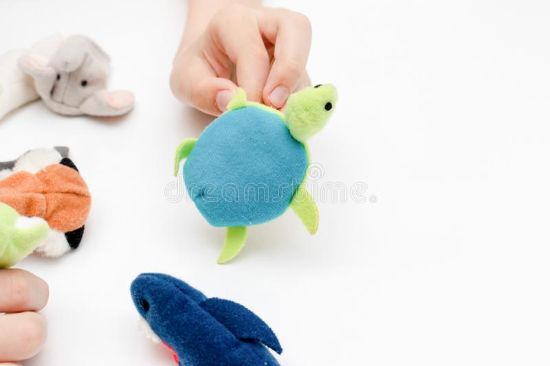 A caucasian boy playing finger puppets, toys, dolls - figures of animals, heroes of the puppet theatre put on fingers of human. Hand royalty free stock image