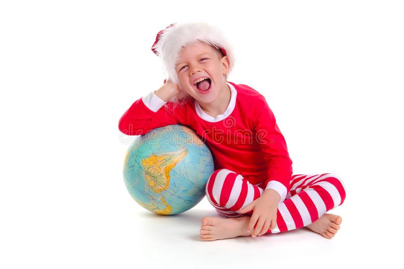 Caucasian boy in red Santa Claus costume and hat smiles at the camera and holds a large globe in his hands on white stock photo