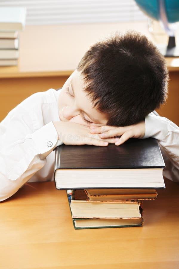 Caucasian boy sleeping on books stock photography