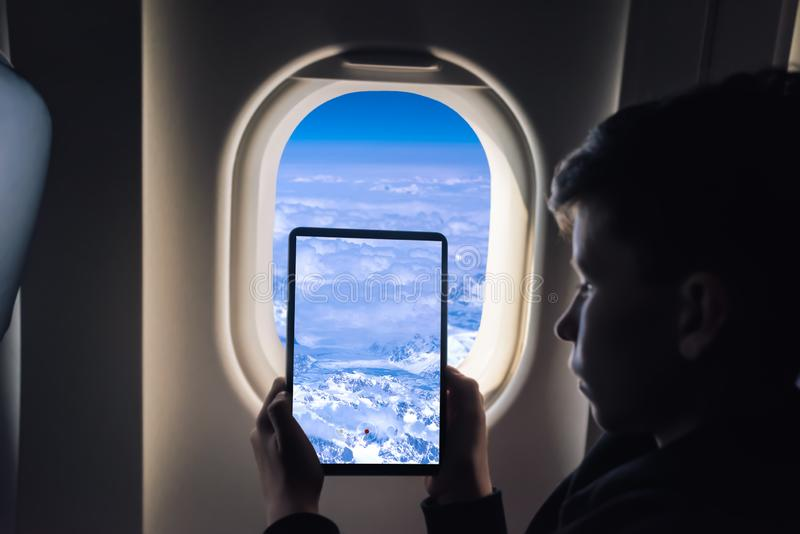 Caucasian boy using tablet pc taking picture through airplane window Greenland glaciers. Caucasian boy using tablet pc taking picture through airplane window royalty free stock photo