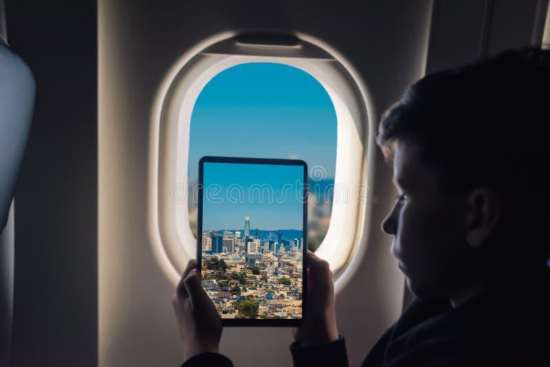 Caucasian boy using tablet pc taking picture through airplane window San Francisco cityscape. California. USA royalty free stock photo