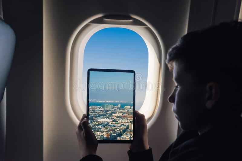 Caucasian boy using tablet pc taking picture through airplane window San Francisco cityscape. California. USA royalty free stock photography