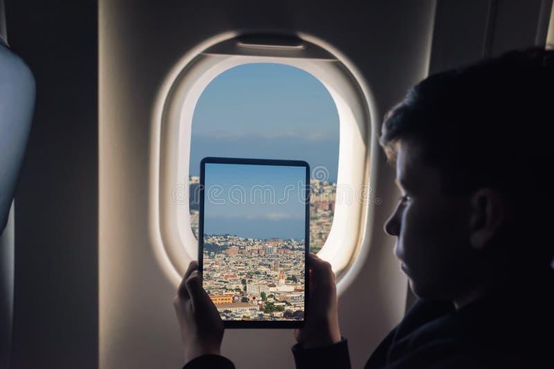 Caucasian boy using tablet pc taking picture through airplane window San Francisco cityscape. California. USA stock image
