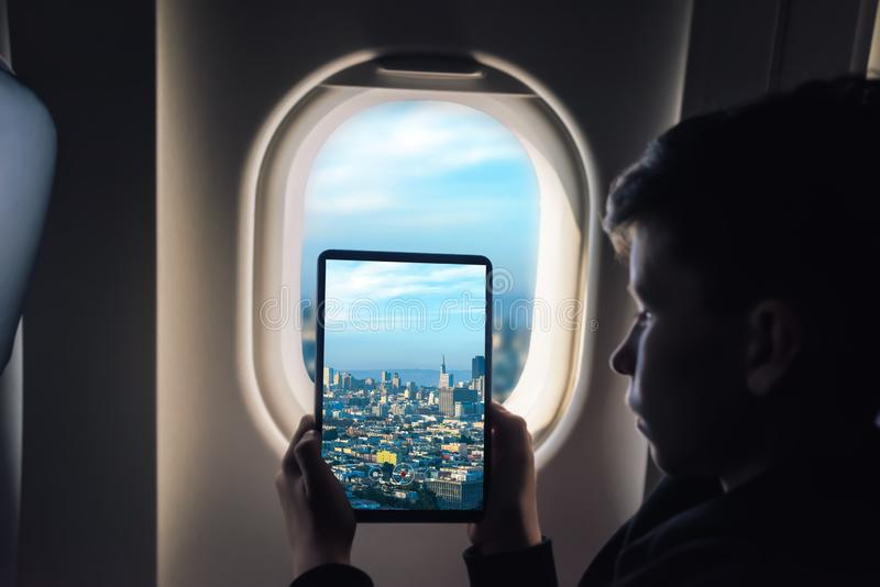 Caucasian boy using tablet pc taking picture through airplane window San Francisco cityscape. California. USA royalty free stock image