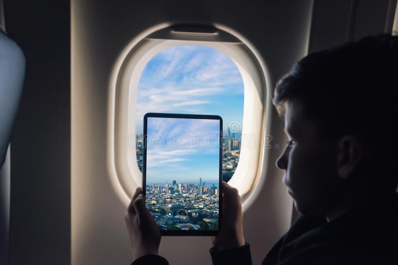 Caucasian boy using tablet pc taking picture through airplane window San Francisco cityscape. California. USA royalty free stock images