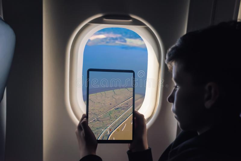 Caucasian boy using tablet pc for taking picture through plane window Salt Ponds in Don Edwards. San Francisco Bay National Wildli. Fe Refuge. California. USA stock images