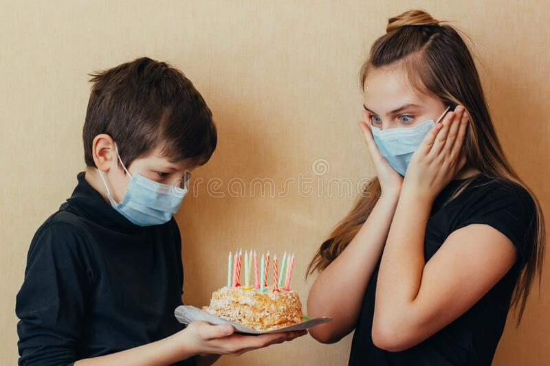 Caucasian brother wishes his sister a happy birthday and gives her a cake with candles. Isolated quarantine celebration without fr. Iends due to outbreaks of royalty free stock images