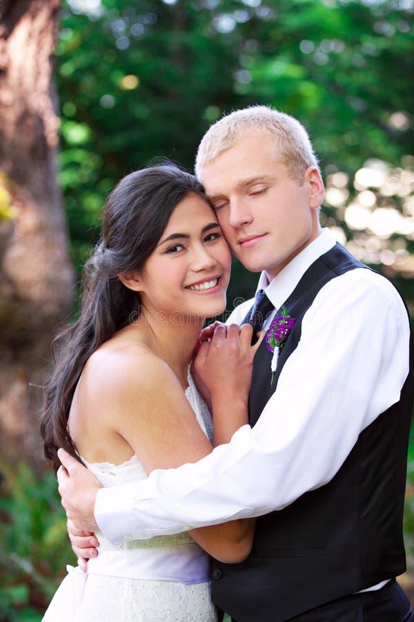 Caucasian brudgum som rymmer hans biracial brud som ler Olik cou arkivfoto