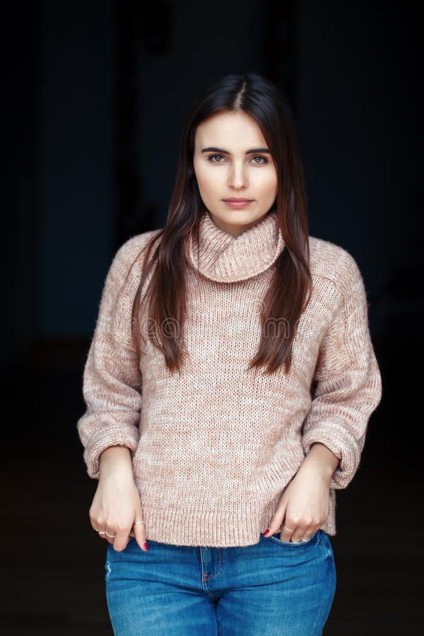 Caucasian brunette young beautiful girl woman model with long dark hair and brown eyes in turtleneck sweater and blue jeans. Portrait of pensive sad serious royalty free stock image