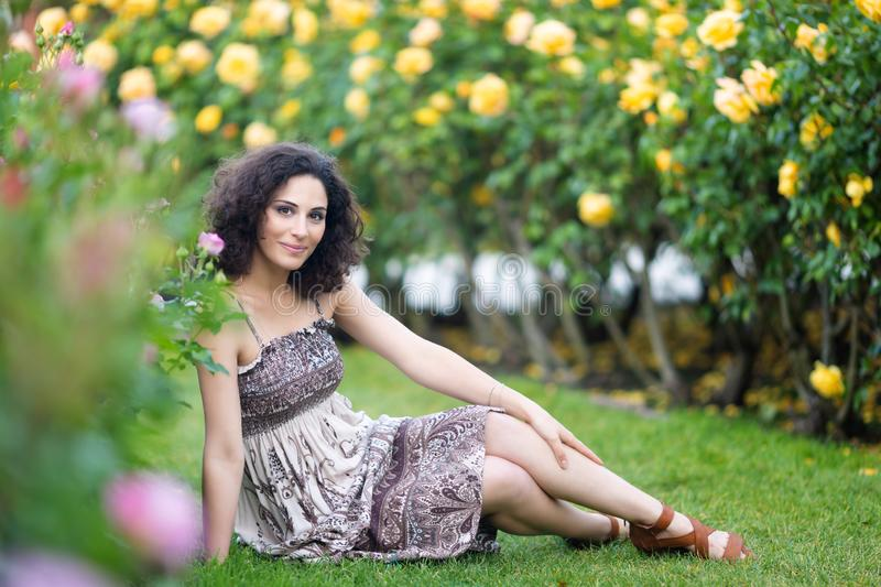 Caucasian brunette young woman sitting on green grass in a rose garden near yellow roses bush, smiling with teeth, looking to the. Camera stock image