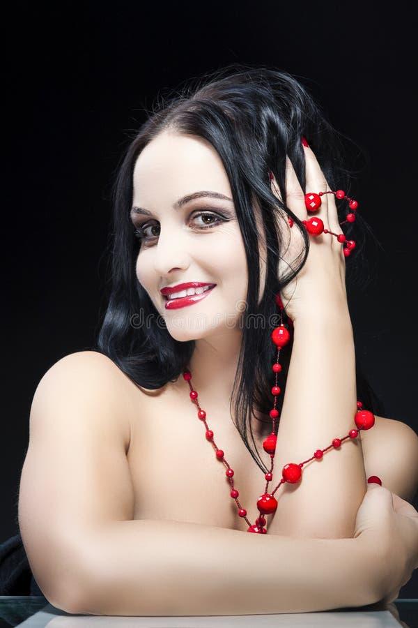 Caucasian brunettkvinna som poserar med långa röda pärlor och trycker på hennes hår arkivfoton