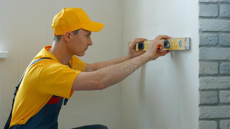 Caucasian builder measuring wall with level tool. royalty free stock image