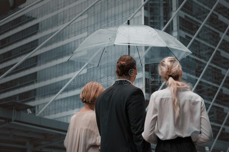 Caucasian business people walking outdoor on street together with umbrella in a groomy day royalty free stock images