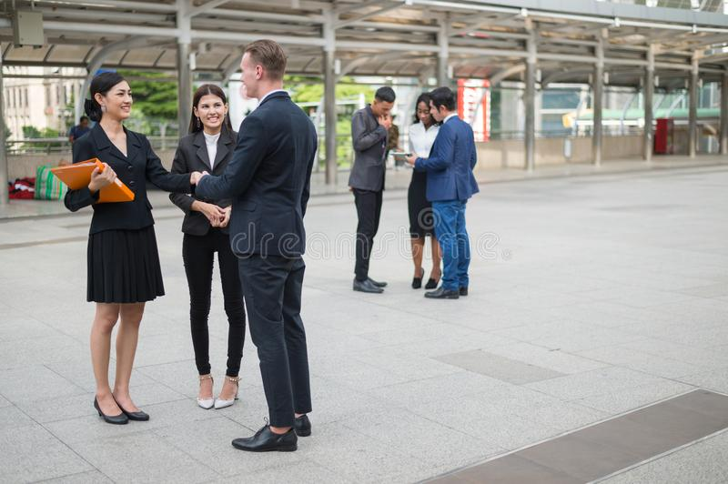 Caucasian businessman and Asian business woman standing and shaking hand for talking about business plan in the future. royalty free stock images
