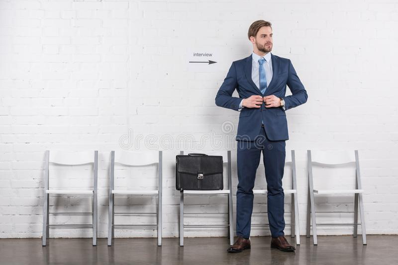 caucasian businessman buttoning suit while waiting royalty free stock images