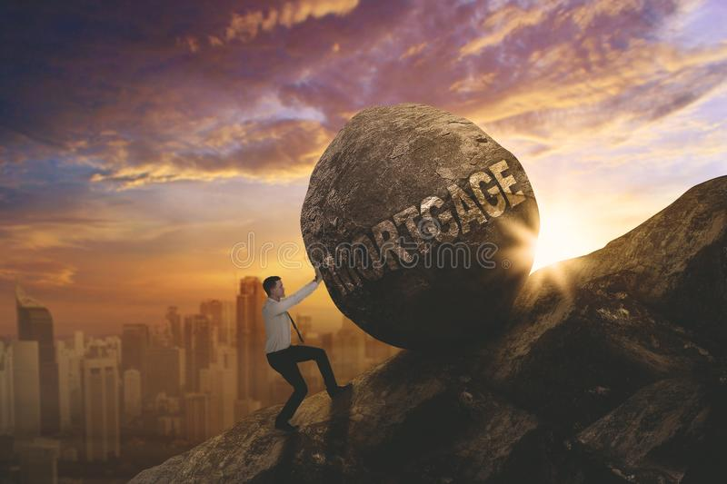 Caucasian businessman pushing mortgage word. Caucasian businessman climbing on the cliff while pushing a stone with mortgage word royalty free stock photo