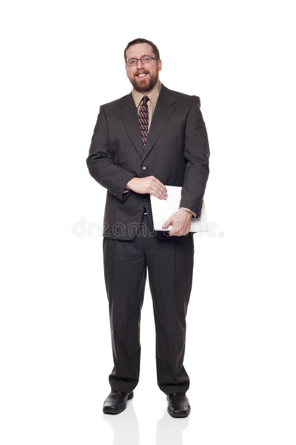Caucasian businessman holding a laptop. Isolated full length studio shot of the side view of a businessman carrying a laptop and looking at the camera stock photo