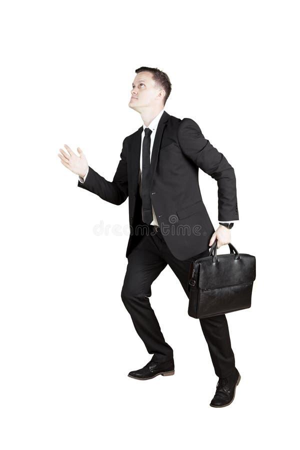 Caucasian businessman posing to step upward. Portrait of a Caucasian businessman carrying a briefcase while posing to step upward, isolated on white background royalty free stock photo