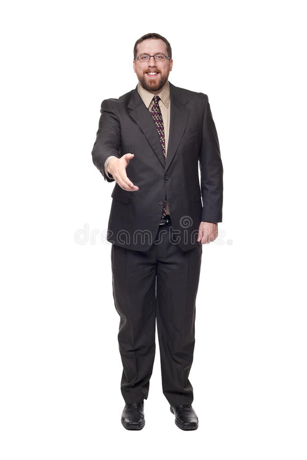 Caucasian businessman reaching shake hands. Isolated full length studio shot of the front view of a smiling businessman reaching out to shake hands with the stock photography