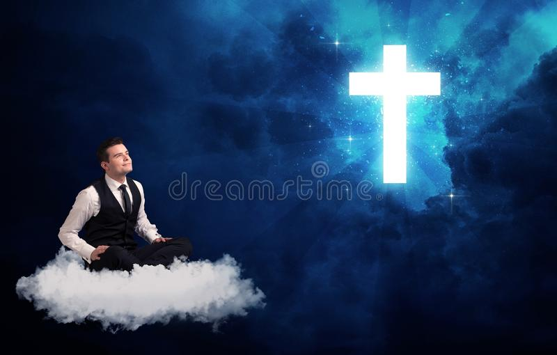 Man sitting on cloud lokking at a cross. Caucasian businessman sitting on a white fluffy cloud looking and wondering at a big bright glowing cross stock photography