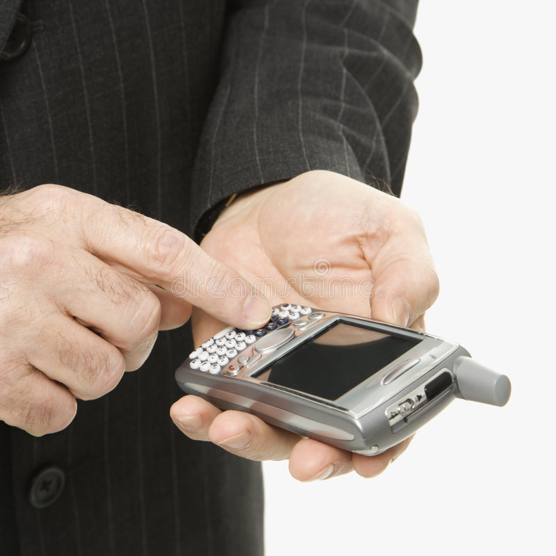 Caucasian businessman using PDA. Close-up of Caucasian middle-aged businessman using handheld PDA stock photography