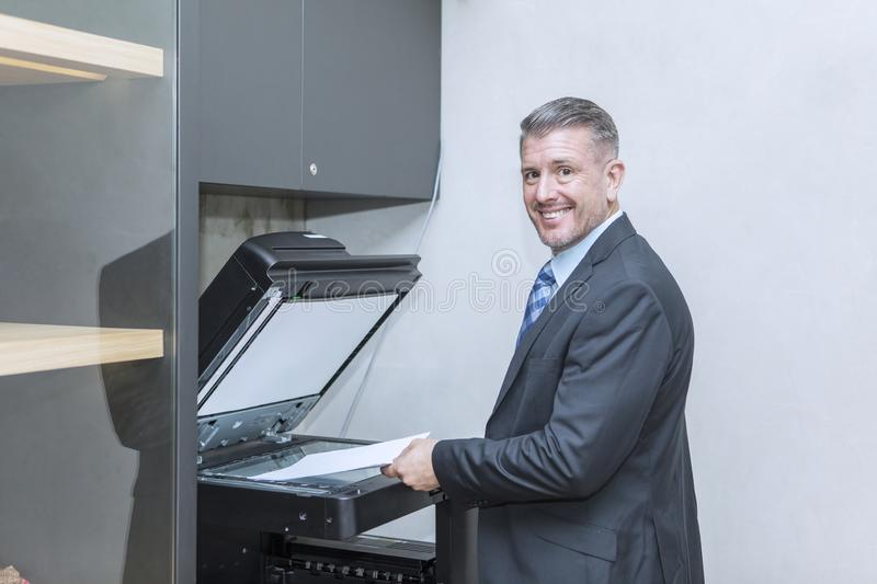 Caucasian businessman using photocopy machine stock image