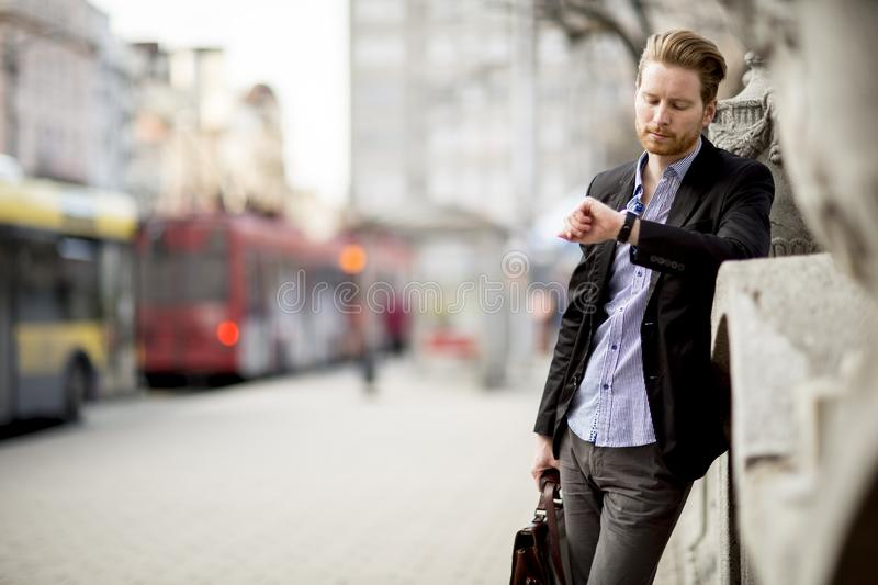 Caucasian businessman waiting outside and looking at his watch. Caucasian businessman waiting outdoor and looking at his watch royalty free stock photo