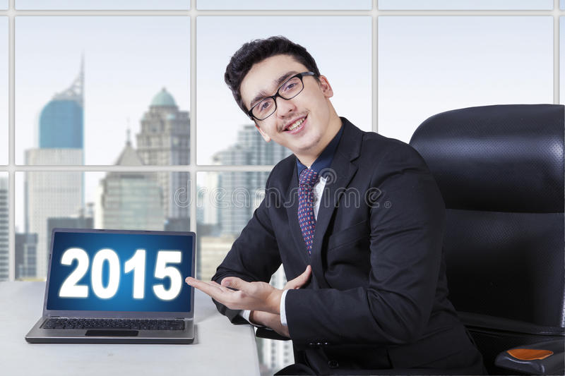 Caucasian businessperson showing number 2015. Friendly businessman smiling at the camera while showing number 2015 on the laptop in the office stock images