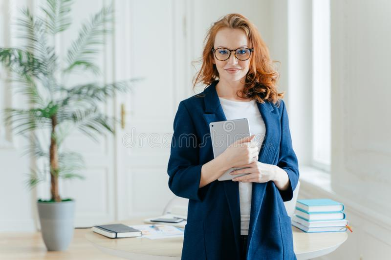 Caucasian businesswoman holds tablet computer, checks balance account, wears optical glasses and formal outfit, waits for royalty free stock photos