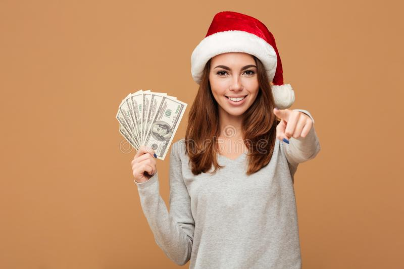 Caucasian cheerful lady wearing christmas hat pointing to you. royalty free stock photo