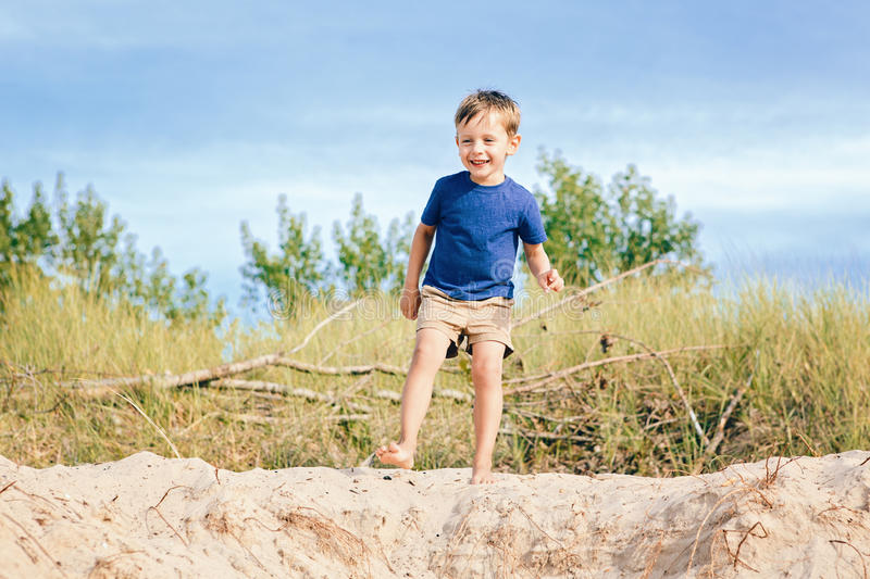 Caucasian child boy playing on sand dunes beach on sunny summer day near forest stock images