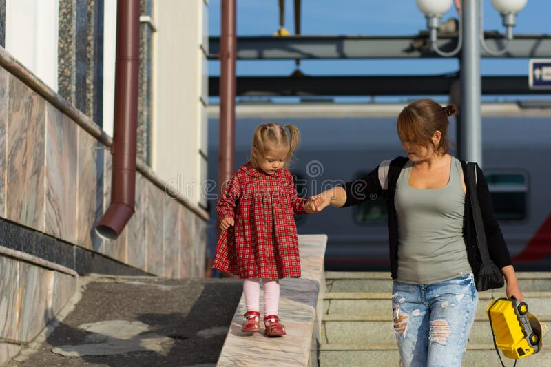 Caucasian child of two years old walking down holding the mother hand supporting woman. Caucasian child of two years old walking down holding mother hand royalty free stock photo