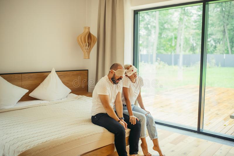 Happy couple relaxing, sitting on bed with mask for sleep stock photos