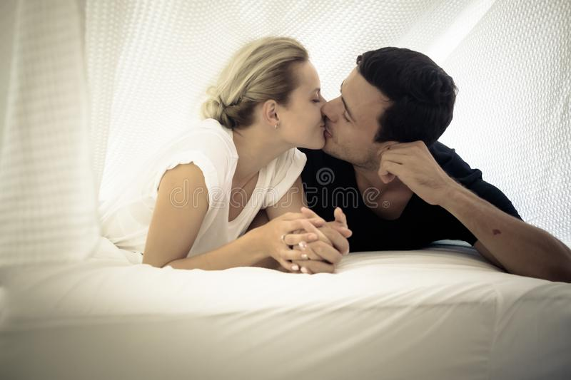 Caucasian couple kissing under the sheets on the bed at home in the bedroom - intimate lifestyle for young people in love - stock images