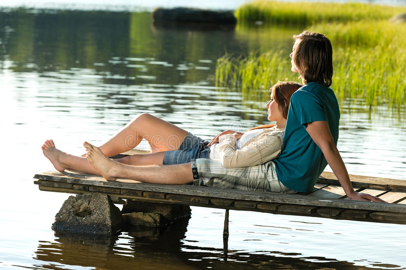 Caucasian couple lounging on pier sunset. Young Caucasian couple lounging on pier by lake sunset royalty free stock photos