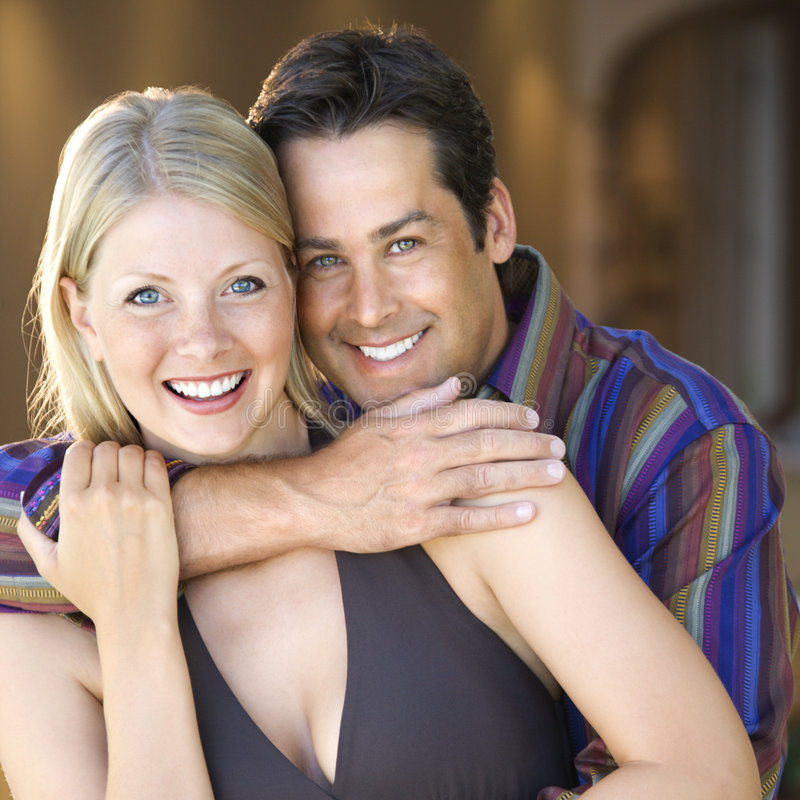 Caucasian couple smiling. Caucasian mid adult couple embracing and smiling at viewer royalty free stock image