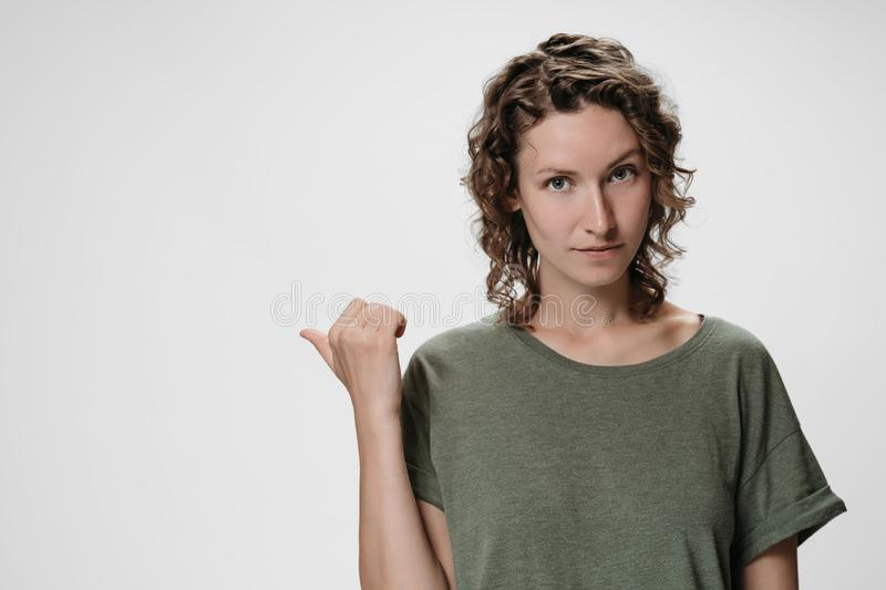 Caucasian curly woman with friendly expression, points aside with thumb, shows free copy. Space for your advertising content on white background. Advertisement royalty free stock image